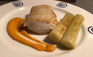 Lomo de merluza, puerros confitados y salsa romesco
