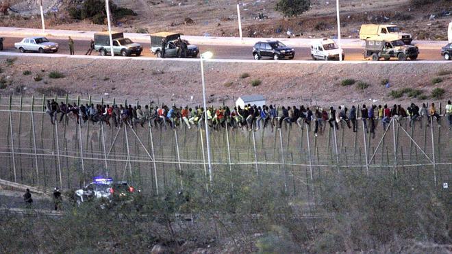 Los inmigrantes encaramados en la valla comienzan a bajarse tras 9 horas